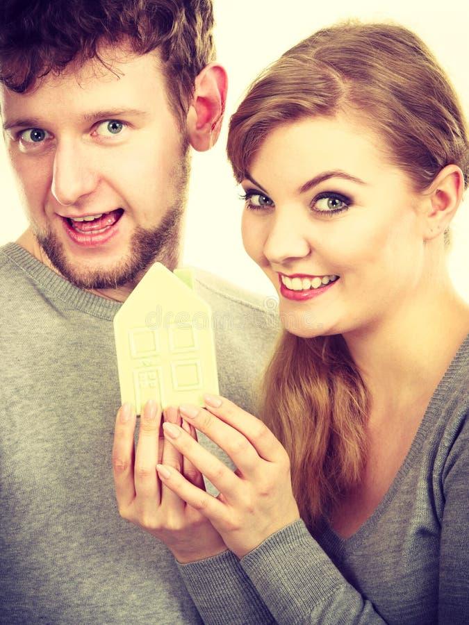Giovani paia innamorate che mostrano simbolo della casa fotografia stock libera da diritti