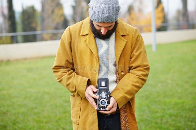 Giovani pantaloni a vita bassa barbuti che prendono foto con la macchina fotografica di TLR immagini stock libere da diritti