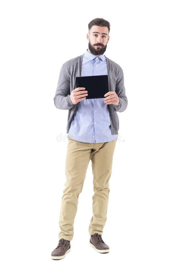 Giovani pantaloni a vita bassa barbuti freschi che tengono e che mostrano il visualizzatore del computer nero in bianco della com fotografie stock libere da diritti