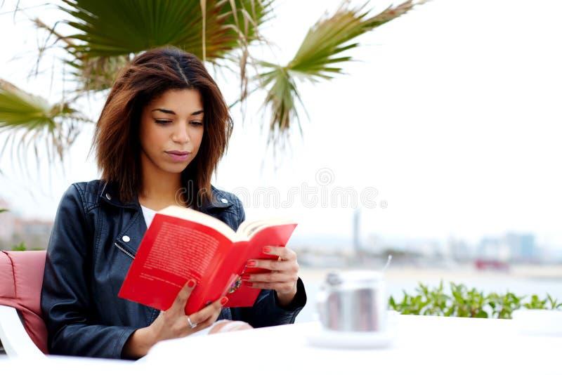 Giovani pantaloni a vita bassa femminili che affascinano libro colto nella caffetteria dell'aria aperta durante il suo tempo di r immagini stock