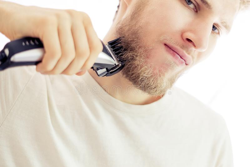 Giovani pantaloni a vita bassa isolati che radono barba con la macchina su fondo bianco fotografia stock