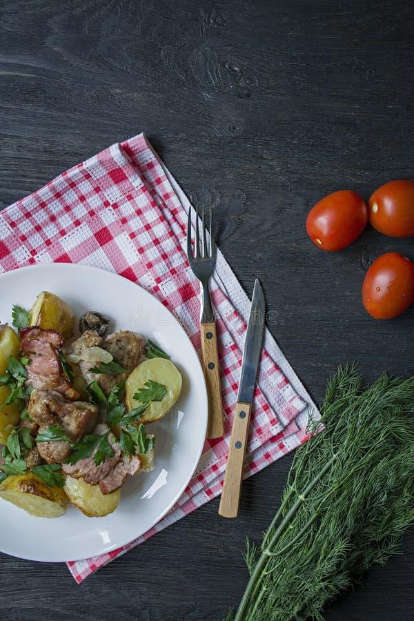 Giovani patate al forno con carne e le verdure Priorit? bassa di legno scura fotografia stock libera da diritti