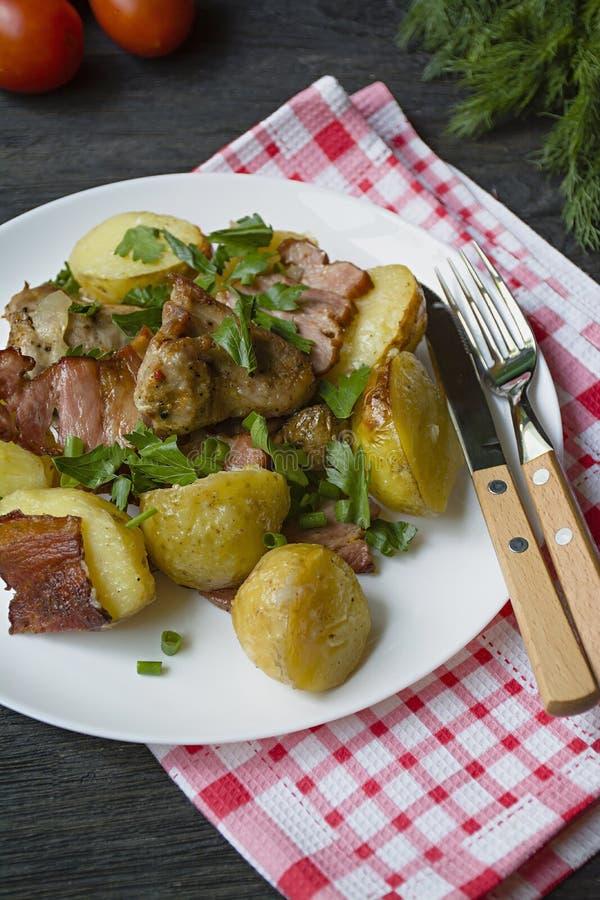 Giovani patate al forno con carne e le verdure Priorit? bassa di legno scura fotografie stock