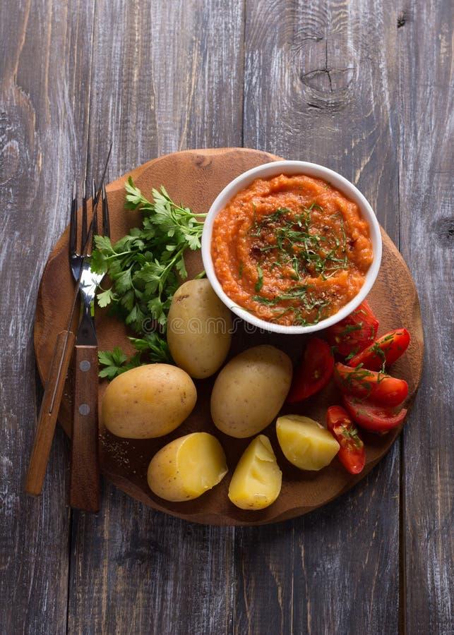 Giovani patate bollite in una buccia con il caviale dello zucchini, le spezie, i pomodori freschi ed il prezzemolo immagini stock libere da diritti