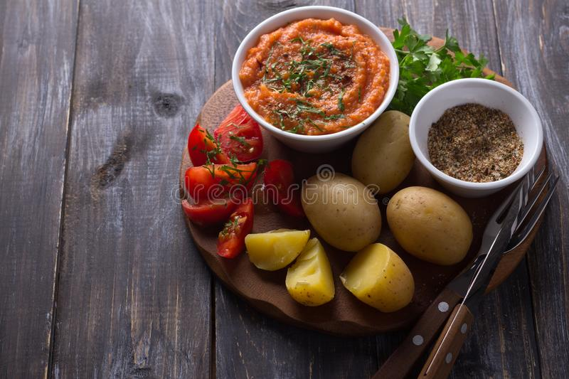 Giovani patate bollite in una buccia con il caviale dello zucchini, le spezie, i pomodori freschi ed il prezzemolo fotografia stock libera da diritti