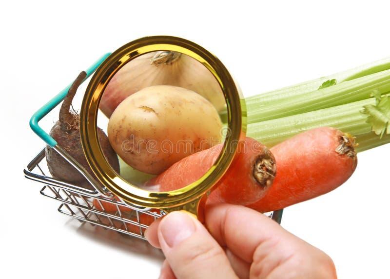 Giovani patate nel canestro di verdure del primo piano del compratore tramite una lente d'ingrandimento immagine stock
