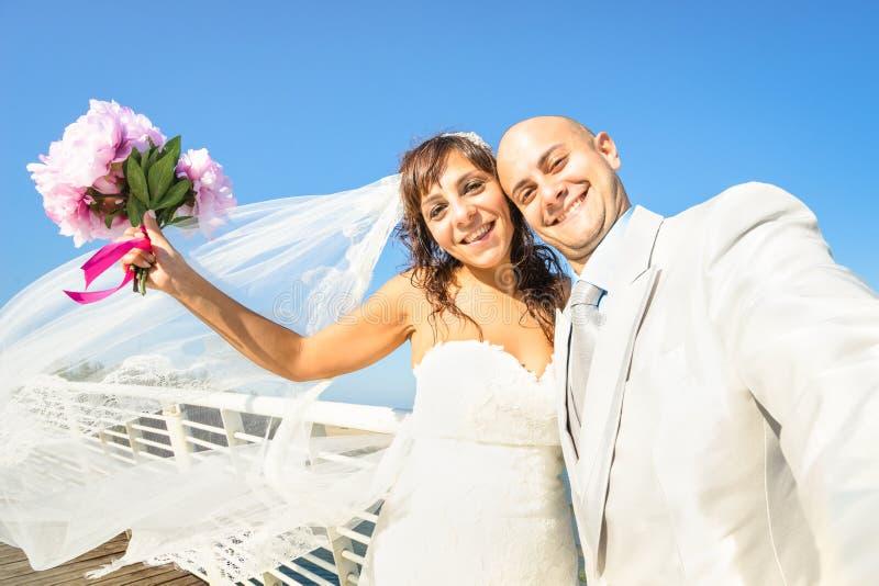Giovani persone appena sposate con il mazzo che prende selfie contro il cielo blu immagine stock libera da diritti