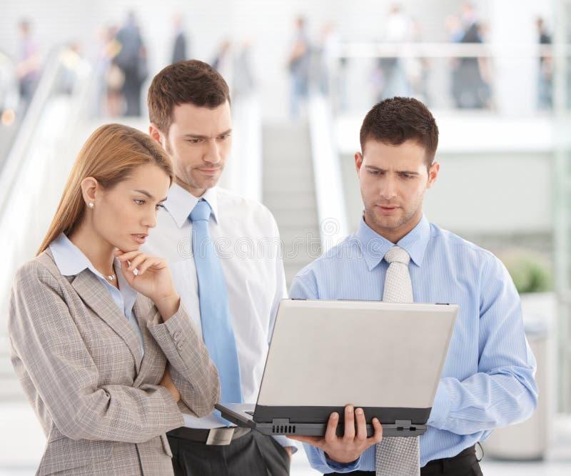 Giovani persone di affari che esaminano lo schermo del computer portatile immagini stock