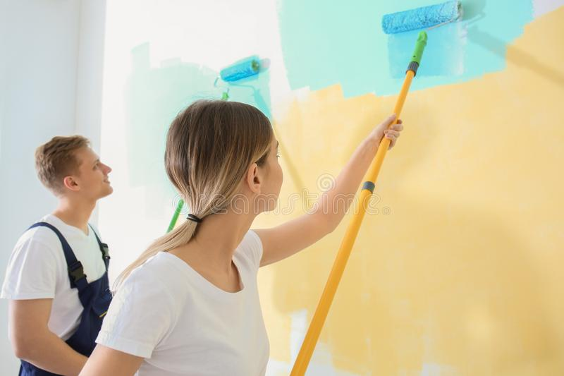 Giovani pittori che per mezzo dei rulli per la ristrutturazione del colore della parete all'interno immagini stock libere da diritti