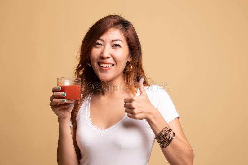 Giovani pollici asiatici della donna su con il succo di pomodoro immagine stock