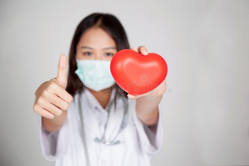Giovani pollici femminili asiatici di medico su con cuore rosso fotografie stock