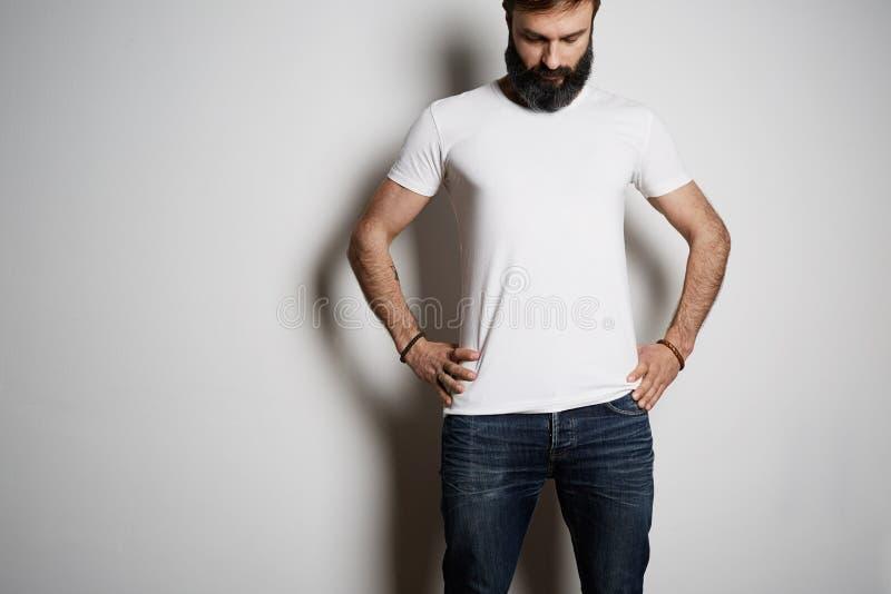 Giovani pose barbute tatuate brutali del tipo in blue jeans e nel cotone super di estate della maglietta bianca in bianco, su fon fotografia stock libera da diritti