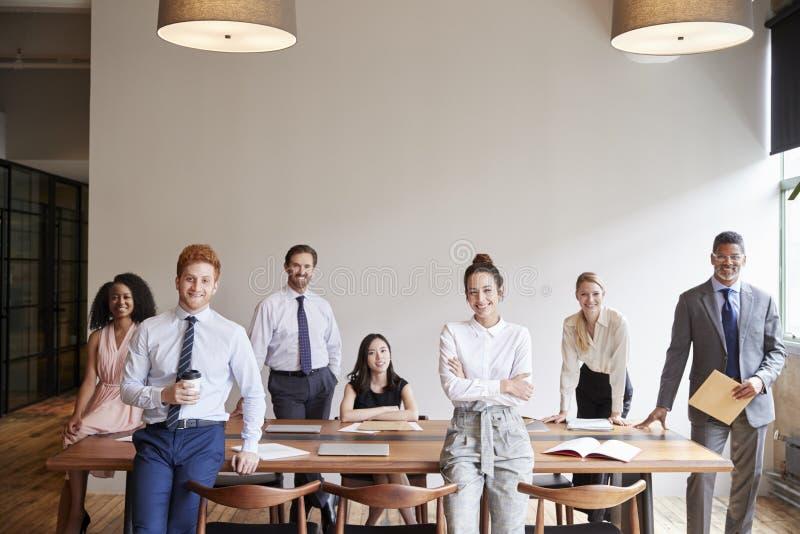 Giovani professionisti ad una riunione d'affari che guarda alla macchina fotografica immagini stock