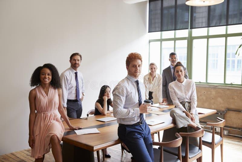 Giovani professionisti in una sala riunioni che guarda alla macchina fotografica fotografia stock