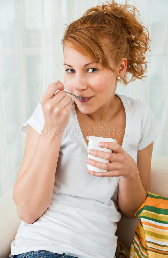 Giovani, ragazza di bellezza che mangia yogurt immagini stock libere da diritti