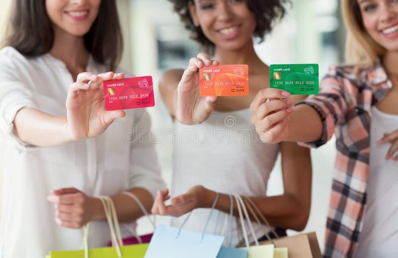 Giovani ragazze attraenti con le carte di credito nel centro commerciale fotografia stock libera da diritti