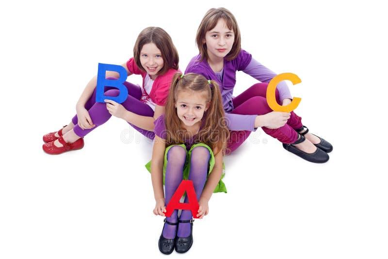 Giovani ragazze del banco che tengono le lettere del ABC immagine stock libera da diritti
