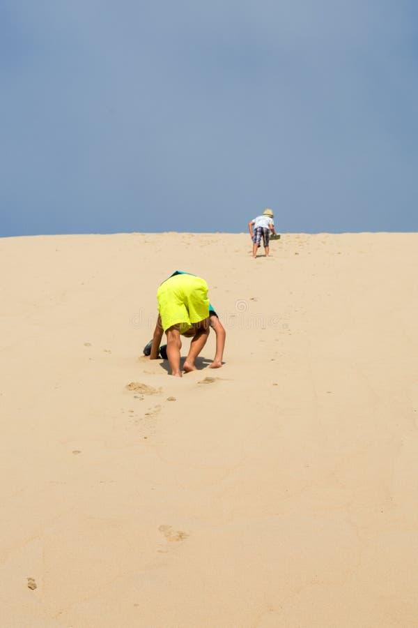 Giovani ragazzi che corrono sulla duna di sabbia immagine stock libera da diritti