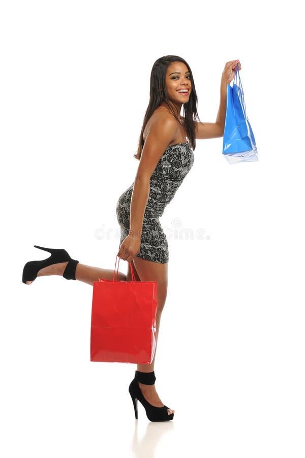 Giovani sacchetti di acquisto della holding della donna dell'afroamericano fotografia stock libera da diritti