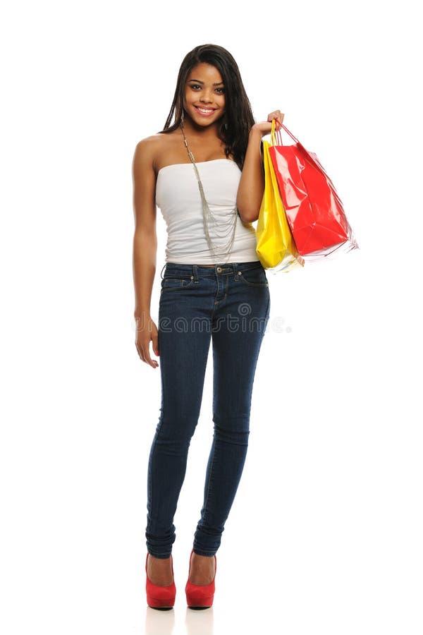 Giovani sacchetti di acquisto della holding della donna di colore fotografia stock libera da diritti