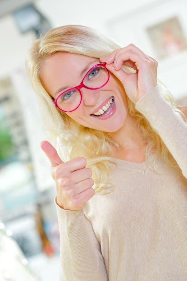 Giovani seemes biondi soddisfatti di nuovi vetri immagini stock