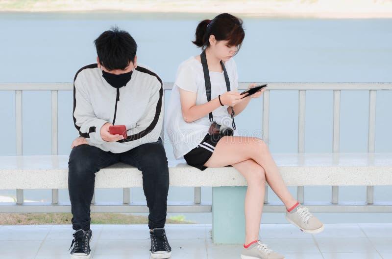 Giovani seri facendo uso degli smartphones che si siedono nel parco fotografia stock libera da diritti