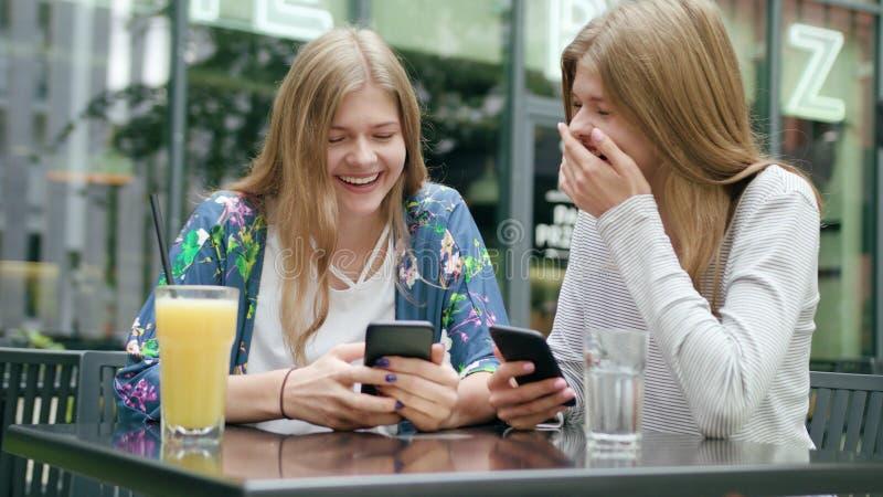 Giovani signore che per mezzo dei loro telefoni all'aperto immagine stock