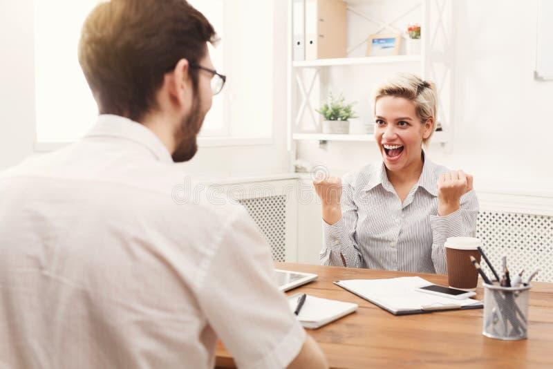 Giovani soci commerciali felici in ufficio con il computer immagini stock