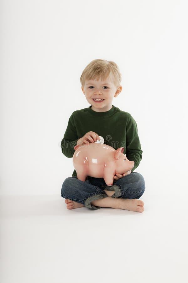 Giovani soldi di risparmio del ragazzo nella Banca di moneta fotografia stock