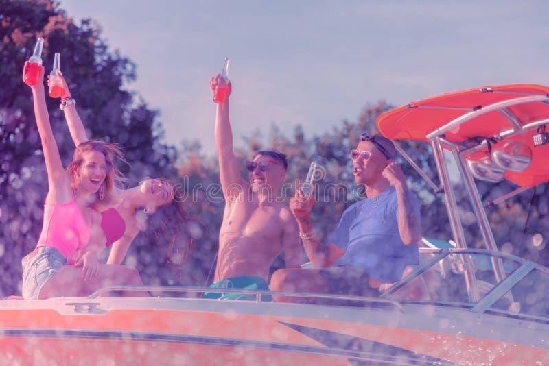 Giovani sorridenti che girano in un yacht moderno fotografie stock