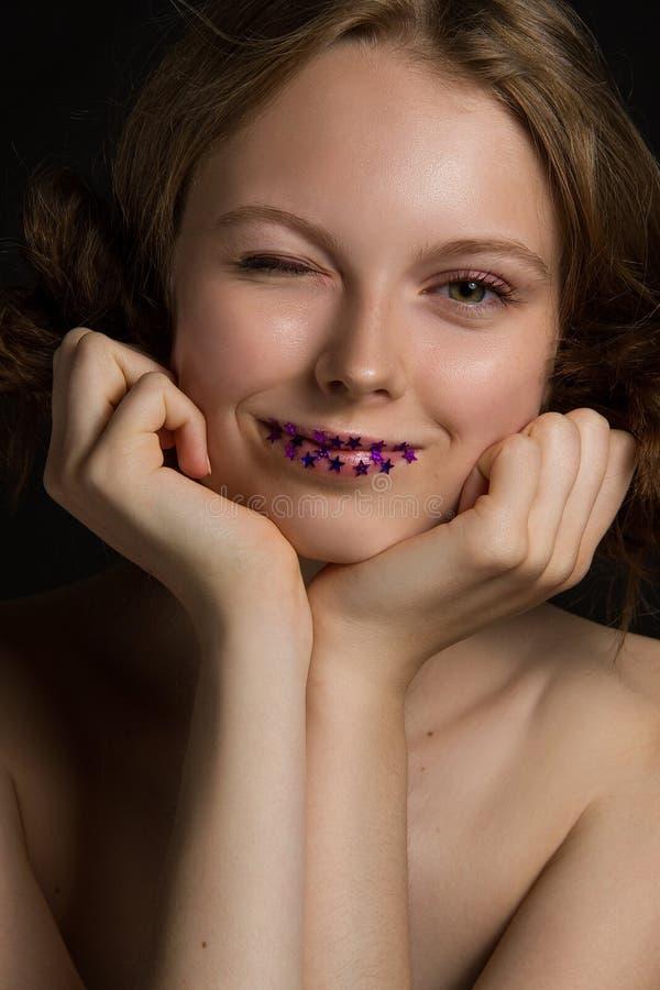 Giovani sorrisi e strizzatine d'occhio impressionanti del modello fotografia stock libera da diritti