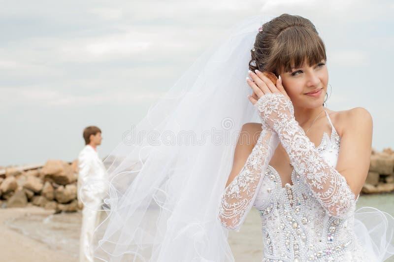 Giovani sposa e sposo sulla spiaggia fotografia stock libera da diritti