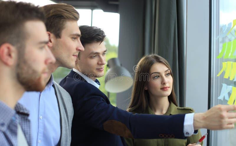 Giovani startup creativi sulla riunione all'ufficio moderno che fa i piani ed i progetti con gli autoadesivi della posta sul vetr immagine stock