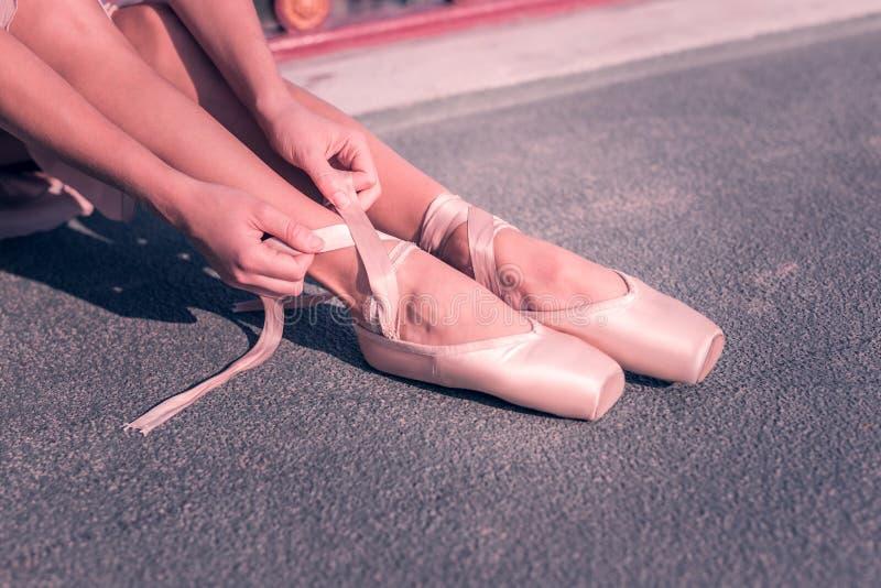 Giovani strisce professionali piacevoli della scarpa della tenuta della ballerina fotografia stock libera da diritti