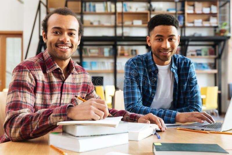 Giovani studenti africani felici degli uomini che si siedono nella biblioteca immagini stock libere da diritti