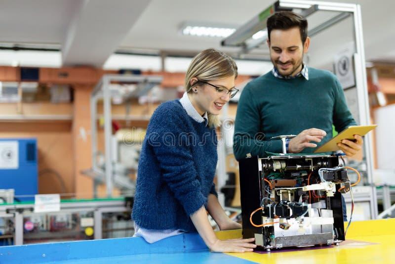 Giovani studenti attraenti della meccatronica che lavora al progetto immagini stock