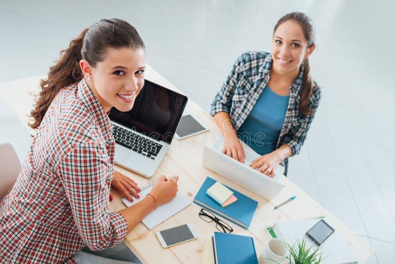 Giovani studenti che fanno il loro compito immagine stock