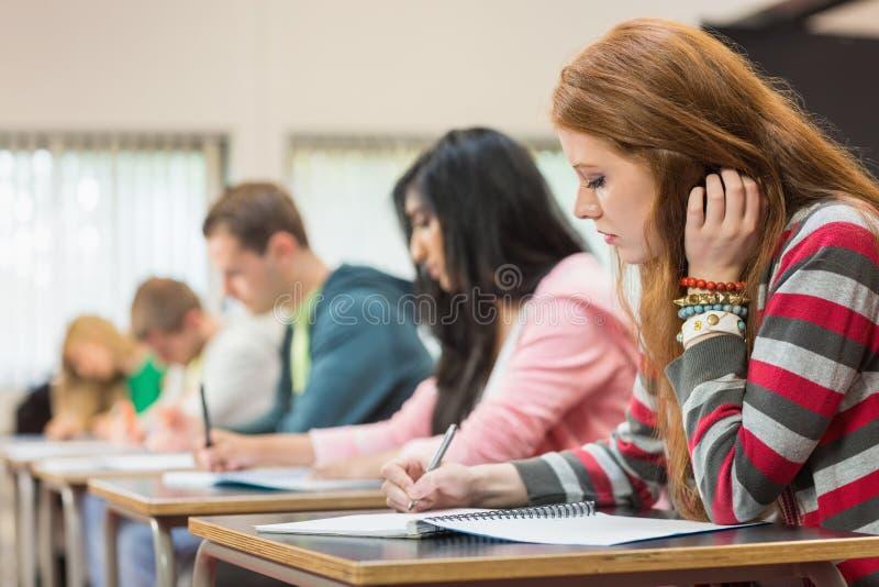 Giovani studenti che scrivono le note nell'aula immagini stock