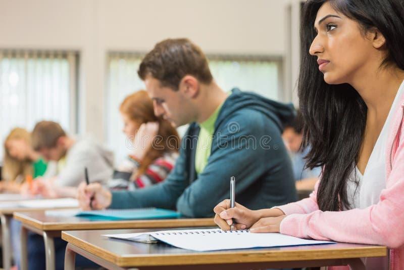 Giovani studenti che scrivono le note nell'aula immagine stock