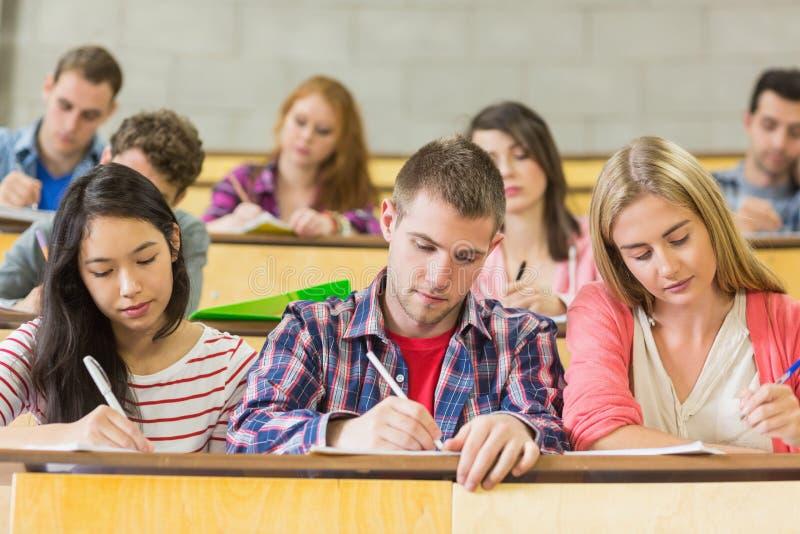 Giovani studenti che scrivono le note nell'aula fotografie stock libere da diritti