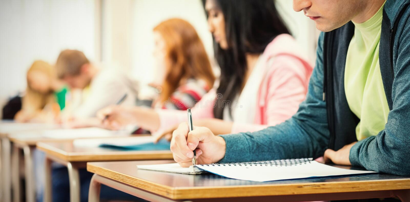 Giovani studenti che scrivono le note nell'aula fotografie stock