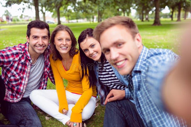 Giovani studenti di college allegri in parco immagini stock libere da diritti