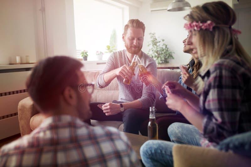 Giovani studenti ed amici che celebrano ahd divertendosi mentre bevendo immagini stock