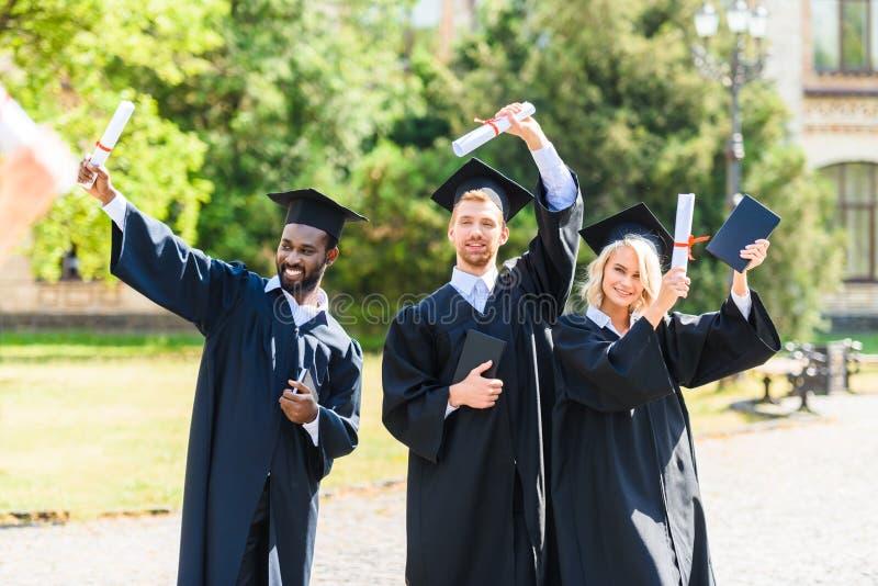 giovani studenti graduati felici in capi immagini stock libere da diritti
