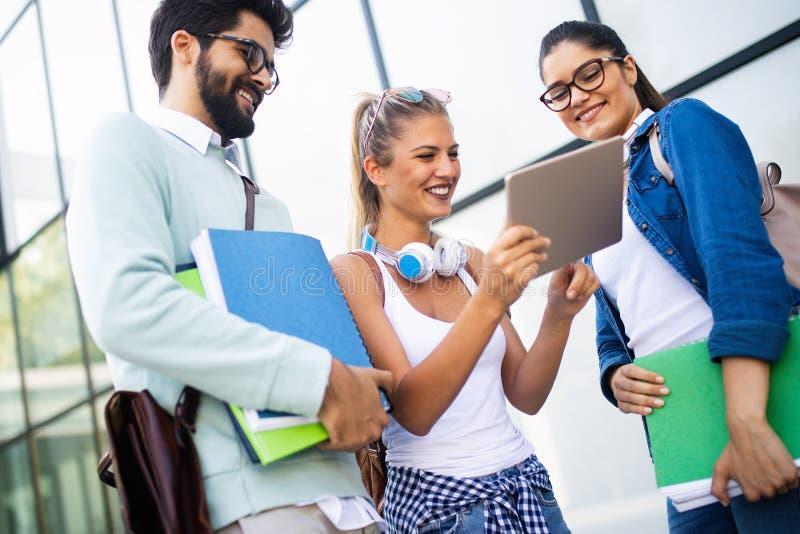 Giovani studenti universitari felici che studiano insieme Gruppo di amici multirazziali in istituto universitario fotografie stock