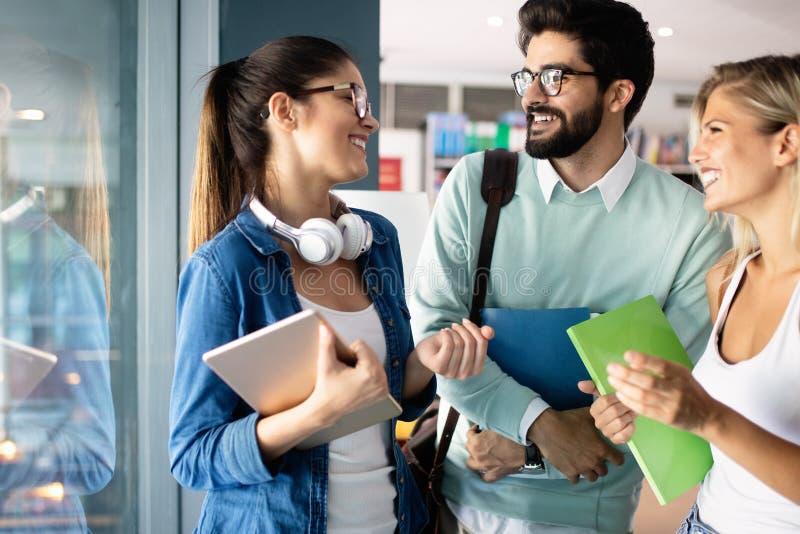 Giovani studenti universitari felici che studiano insieme Gruppo di amici multirazziali in istituto universitario immagini stock libere da diritti