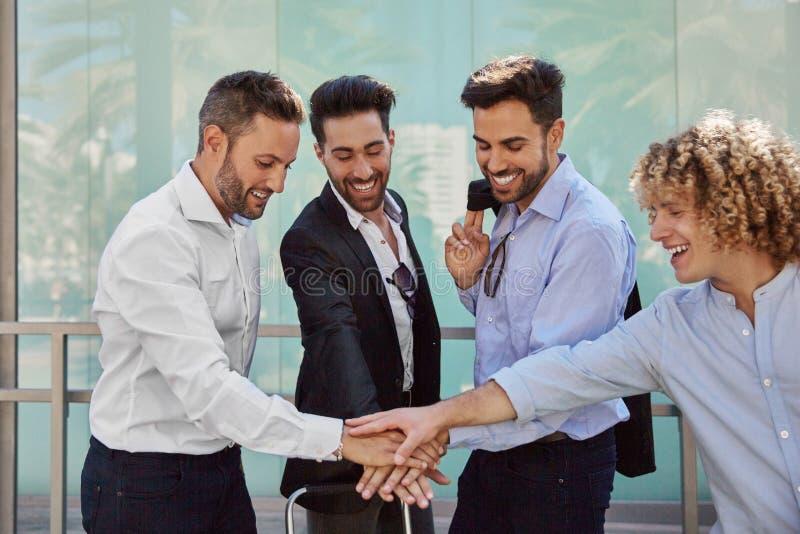 Giovani uomini d'affari che si tengono per mano insieme nel gesto di unità immagini stock libere da diritti