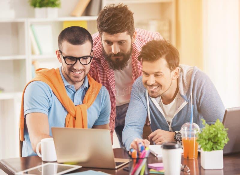 Giovani uomini d'affari nello stile casuale facendo uso del computer portatile fotografie stock