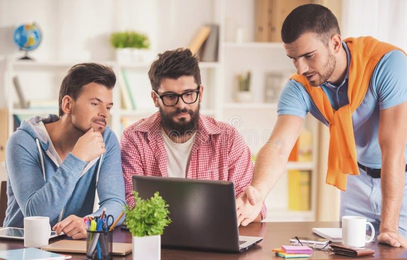Giovani uomini d'affari nello stile casuale facendo uso del computer portatile immagine stock