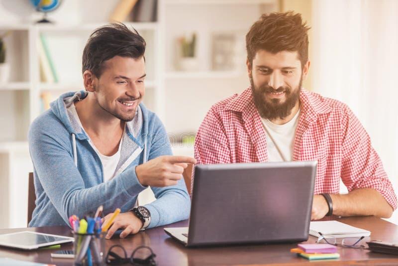 Giovani uomini d'affari nello stile casuale facendo uso del computer portatile fotografia stock libera da diritti